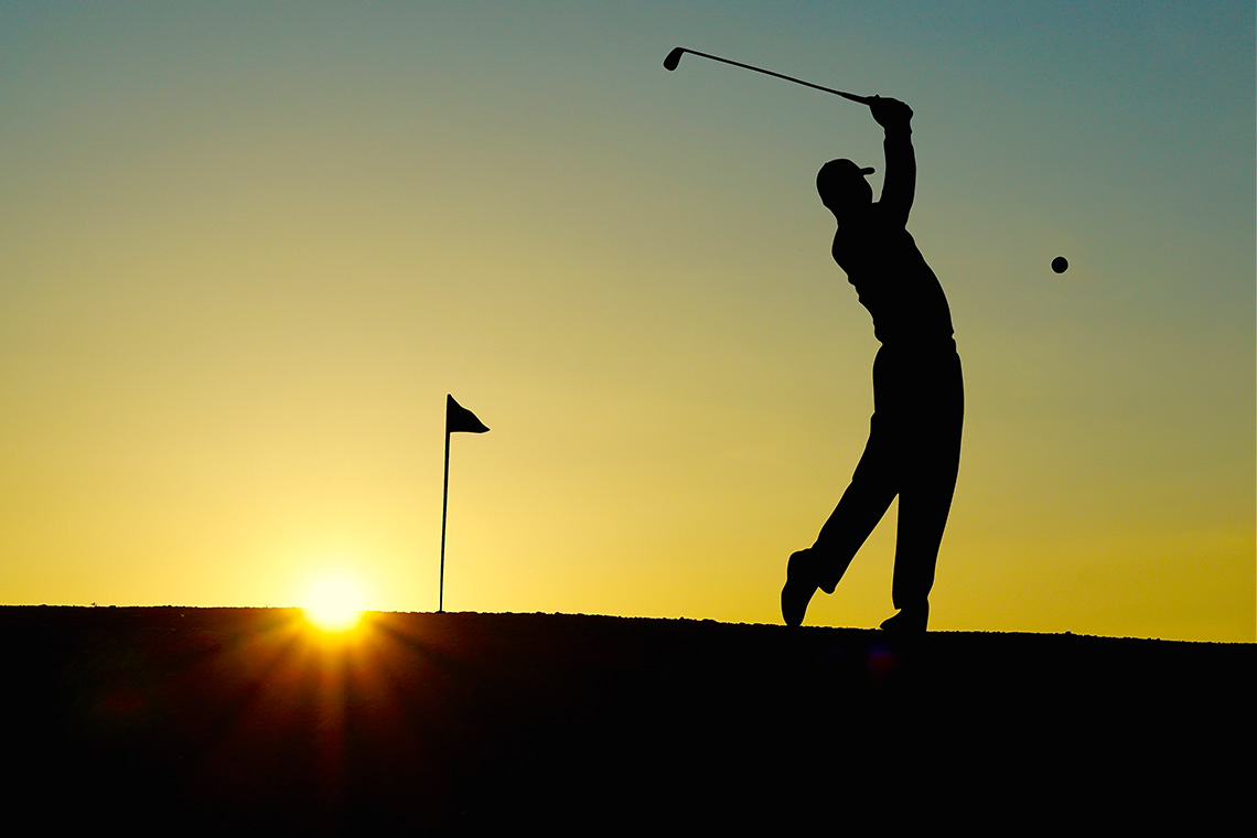 Golfer following through during sunset